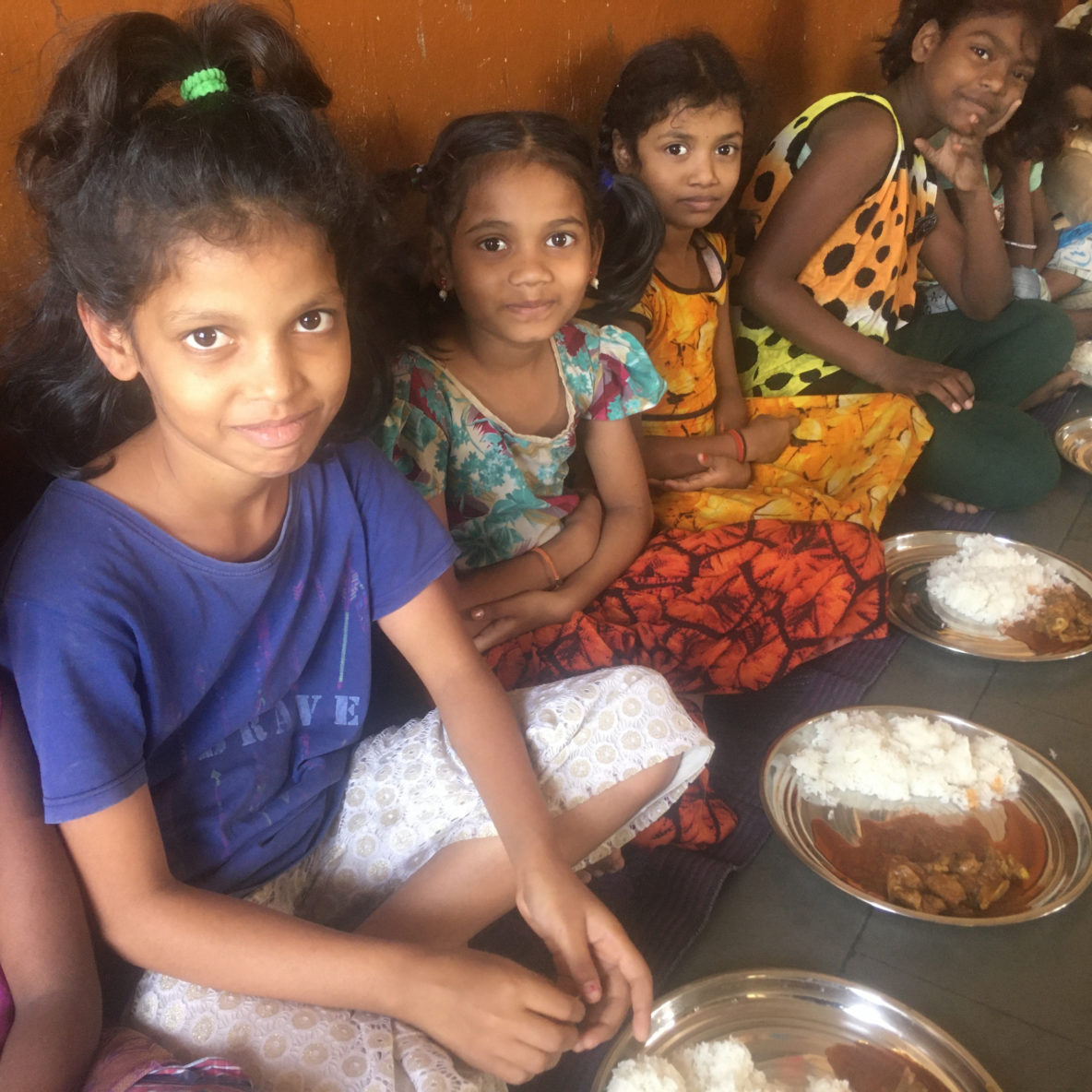 Four child residents at Rainbow Homes smile at camera whilst sitting down to eat lunch.
